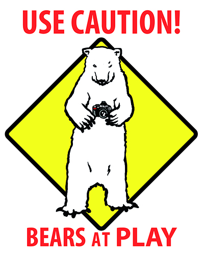Ink design in the form of a warning sign showing a polar bear holding a camera with the words 'Use Caution', 'Bears at Play'.